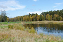 Autumn at the golfcourse. Water and grass and a beutiful sky stock photography
