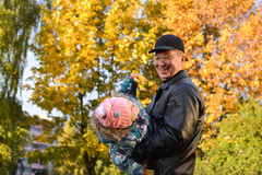In autumn grandfather and granddaughter. In gold autumn grandfather keeps on hand  granddaughter with a smile Royalty Free Stock Photo