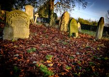 Autumn graveyard showing ancient graves within a carpet of fallen leaves. Royalty Free Stock Photos