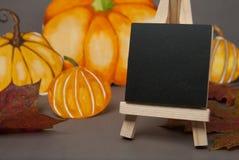 Autumn, halloween pumpkins and mini blackboard chalkboard and maple leaves. Grey backgroud, copy space. Autumn, halloween pumpkins and mini blackboard stock photo