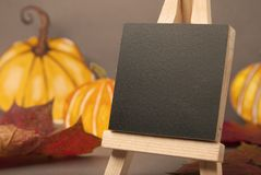 Autumn, halloween pumpkins and mini blackboard chalkboard and maple leaves. Grey backgroud, copy space. Autumn, halloween pumpkins and mini blackboard royalty free stock images