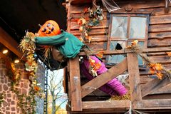 Autumn or Halloween scene with Jack o Lantern head scarecrow. Halloween scarecrow with Jack o Lantern head. Autumn scene at a spooky house royalty free stock image