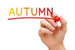 Autumn Handwritten With Marker. Hand writing Autumn concept with different warm colored markers on transparent glass board royalty free stock image