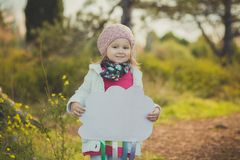 Autumn happy little girl has fun playing with fallen golden leaves Stock Photos