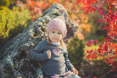 Autumn happy little girl has fun playing with fallen golden leaves Royalty Free Stock Photography