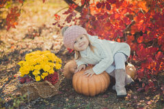 Autumn happy little girl has fun playing with fallen golden leaves Stock Photo