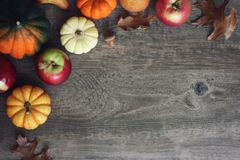 Autumn Harvest Background with Apples, Pumpkins, Pears, Leaves and Acorn Squash Border Over Wood, Shot Directly Above. Fall Harvest Background with Apples Royalty Free Stock Images