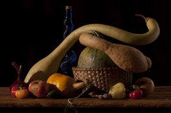Autumn harvest composition. Still life with basket, a blue glass bottle and vegetables stock photo