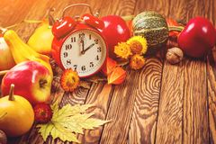 Autumn harvest concept. Fall fruit and vegetables on wooden background. Thanksgiving day. Autumn card with vintage alarm clock, co. Py space. Fall time change royalty free stock photos