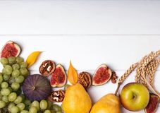 Autumn fruits, nuts and wheat on the white background, top view. Autumn harvest concept: fruits, nuts and wheat on the white background, top view stock images