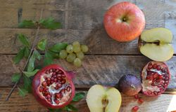 Autumn harvest concept - fruits on wooden table. Selective focus. Space for text. apple pomegranate grapes figs stock photos