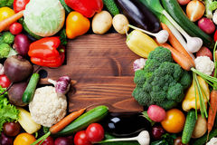 Autumn harvest farm vegetables, root crops and wooden cutting board top view with copy space for text. Healthy food background. Stock Photo