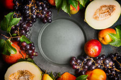 Autumn harvest fruits and vegetables around blank dark vintage dish, top view Royalty Free Stock Images