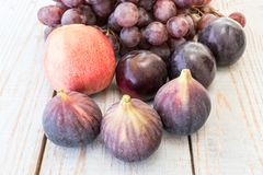 Autumn harvest with grapes, plums, figs, apples. Healthy organic fruit and vegetables. Thanksgiving organic food background Royalty Free Stock Images