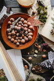Autumn harvest of nuts. On a dark wooden background among books and notebooks Stock Photography