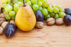 Autumn harvest. Pear, plums and green and blue grapes on wooden background Stock Photo