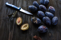 Autumn harvest - plum on the table, cut with a knife Royalty Free Stock Photos