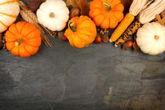 Autumn harvest top border over a slate background. Autumn harvest top border with pumpkins, leaves and nuts over a slate stone background stock photo