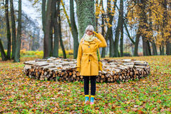 Autumn has come. Young woman standing surround by yellow autum leafs Stock Photo