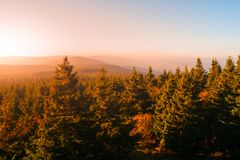Autumn haze illuminated by sun above mountain peaks, Eagle Mountains, Orlicke hory, Czech Republic.  Royalty Free Stock Photos