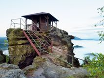 Autumn heavy fogy scene. Wooden cabin on main peak of rock Stock Images