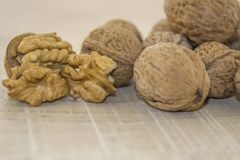 Walnuts on a wooden base. Autumn is here, walnuts in the shell and the core on a wooden surface Stock Images
