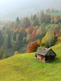 Autumn hills with old house. This picture shows the autumn hills with an old wood house Royalty Free Stock Photo