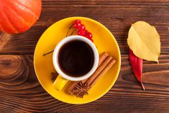 Autumn horizontal banner with yellow, red leaves, pumpkins, cup of coffee and guelder rose on brown wooden background. Stock Photo