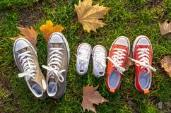 Autumn image of family shoes sneakers gumshoes on grass in sunset light in outdoors family lifestyle royalty free stock photos