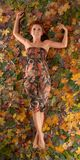 Autumn image with a girl lying in fallen leaves Royalty Free Stock Images
