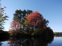 Autumn Island on the Water. A lazy day spent fishing from a canoe in the fall in New England Stock Images