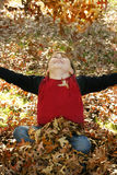 Autumn Joy. A boy throws a pile of leaves overhead and watches them fall Royalty Free Stock Images