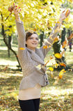 Autumn joy. Young girl playing with autumn leafs Royalty Free Stock Photo