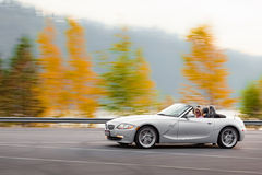 Autumn joy ride. Beautiful young woman driving fast in a convertible enjoying the view and color change of the season in north america