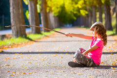 Autumn kid girl with camouflage pants sitting in trees track Royalty Free Stock Images