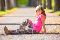 Autumn kid girl with camouflage pants sitting in trees track Royalty Free Stock Photos