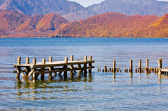 Autumn Lake. Old jetty on a lake set against mountains with autumn leaves Stock Photo