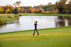 Autumn, lake, golf course. Young adult woman running. On the green grass of the golf course Stock Photo