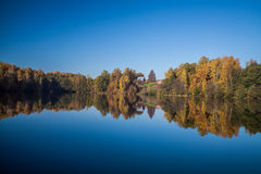 Autumn lake landscape. Autumn landscape, coloured forest on the lake bank, village on the hill, house. Great reflections on the absolutely flat water surface Stock Photo
