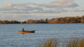 Autumn lake and lonely boat with fisherman stock video footage