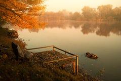 Autumn lake. Pier and adirondack on autumn lake Royalty Free Stock Images