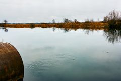 Autumn lake with a pipe stock photo