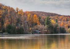 Autumn Lake Reflections. Colorful autumn foliage casts its reflection on the calm waters Royalty Free Stock Image