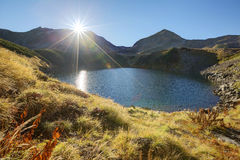 Autumn lake scenery with bright sunlight shining above Mount Tateyama Stock Photos