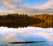 Autumn lake. During sunset with a log floating in the foreground Royalty Free Stock Photos
