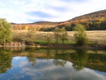 Autumn lake. Water reflection calm silence surface mirror yellow tress forest warm Stock Photo