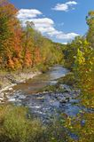 Autumn Landscape. Autumn trees and creek with blue, puffy clouded sky Royalty Free Stock Image