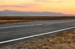 Autumn landscape with an asphalt road and spectacular sunset above mountains on horizon stock photo