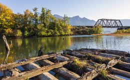 Autumn landscape of the bay on the Columbia River with railway b. Autumn landscape with an old ruined rotten wooden pier in the bay of the Columbia River with royalty free stock image