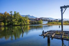 Autumn landscape of the bay on the Columbia River with train pas. Aun landscape with an old ruined rotten wooden pier in the bay of the Columbia River with royalty free stock photo